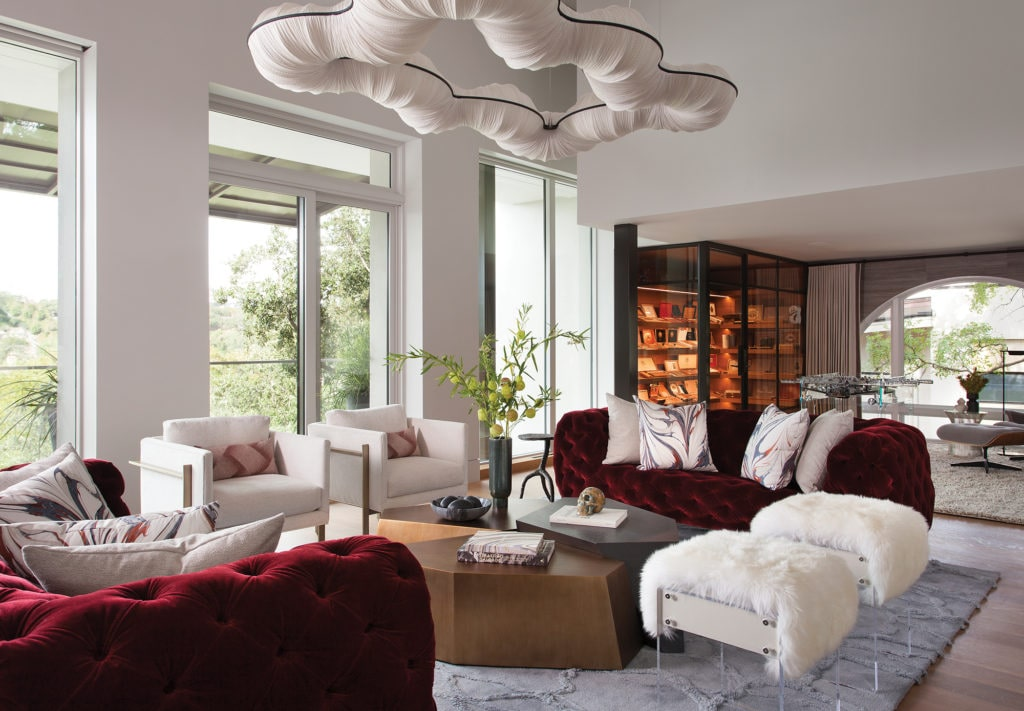 The living room features large custom silk light fixtures and burgundy velvet seating. It opens to the large walk-in humidor.