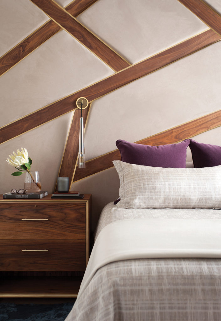 The primary suite includes a custom suede and walnut headboard with brass inlay details and LED lighting.