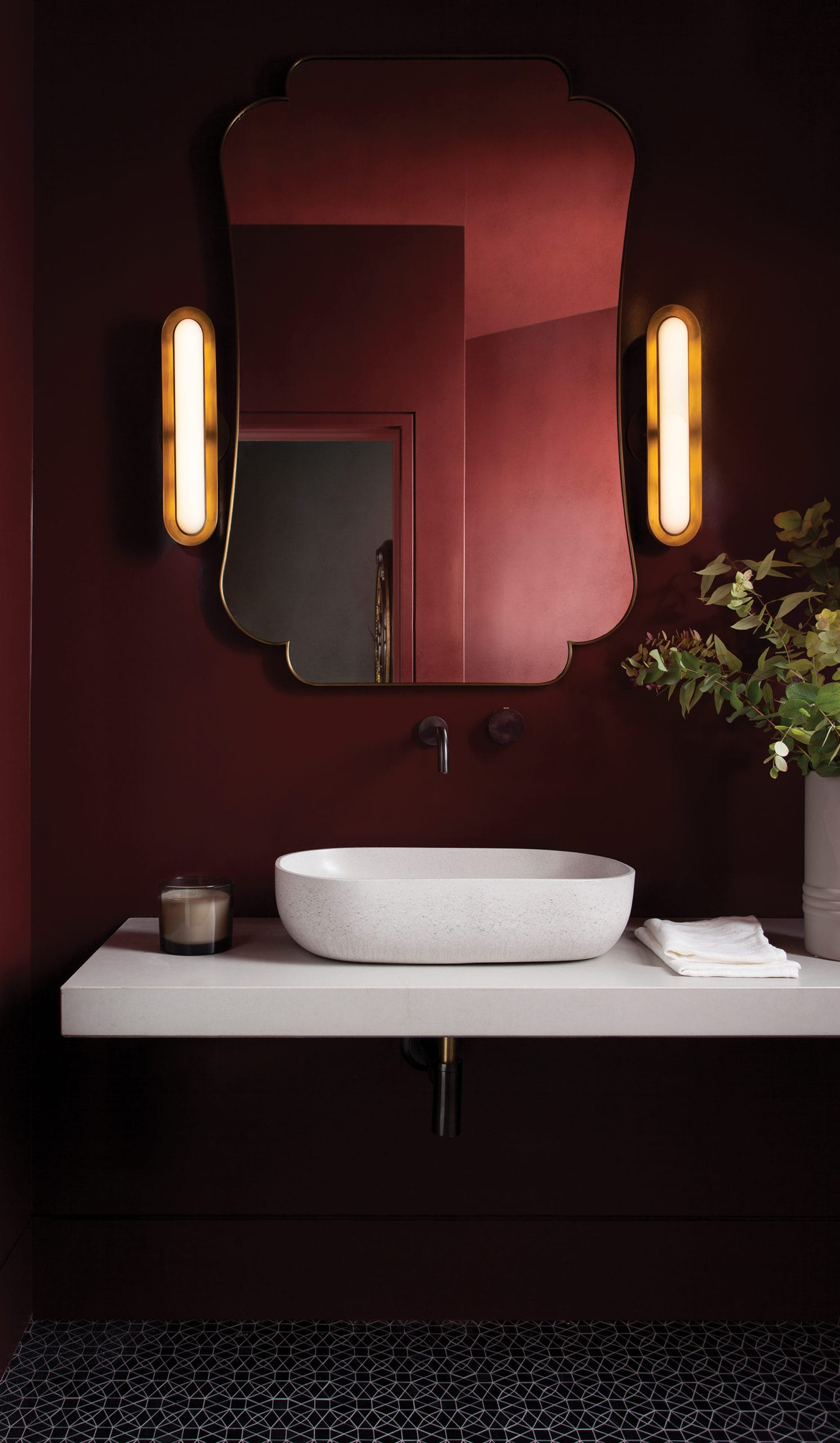 This deep-red powder bathroom has a cantilevered countertop and concrete vessel sink.